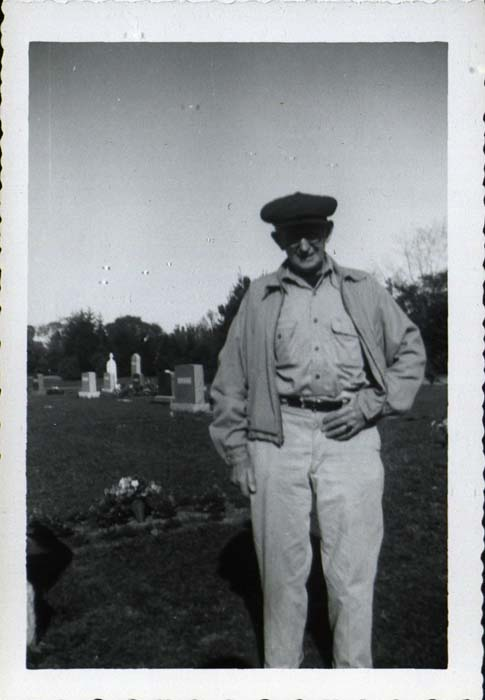Photograph, man standing in cemetery