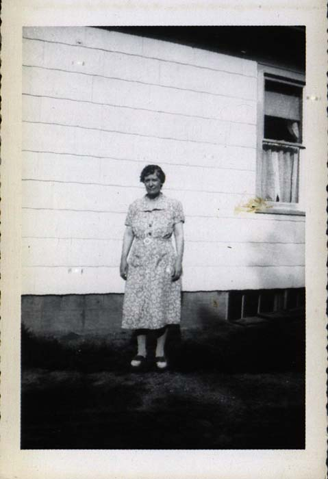 Photograph, woman in front of house