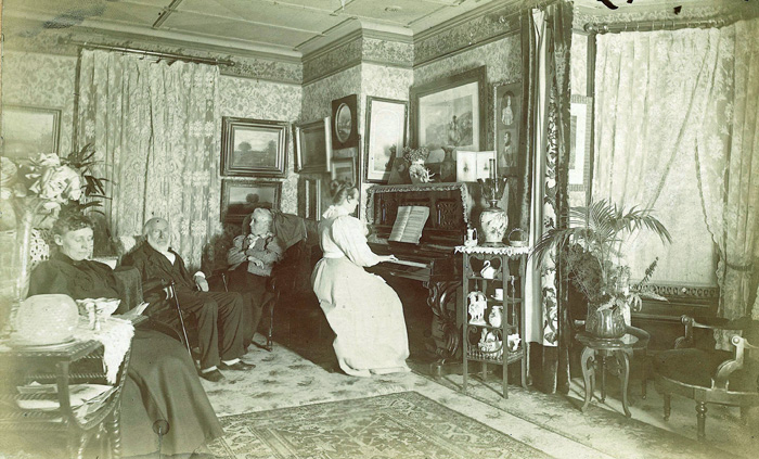 Bertha McGonegal playing piano in the parlor
